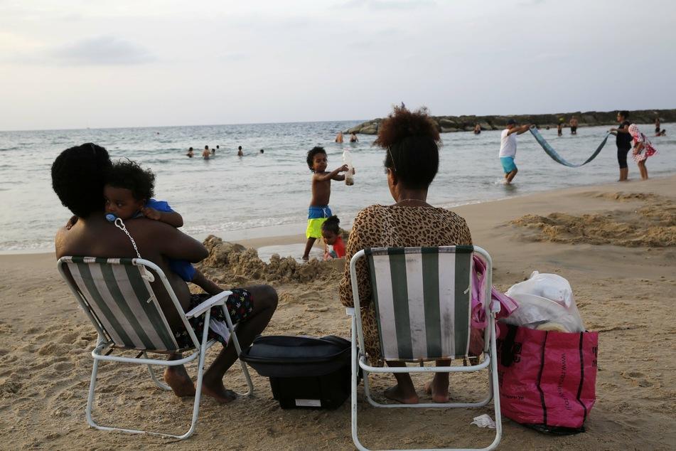 Menschen genießen das warme Wetter am Strand von Aschkelon.