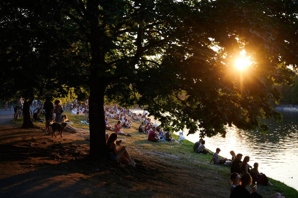 Viele Menschen sitzen bei sehr warmem Wetter in der Abendsonne am Ufer des Landwehrkanales.