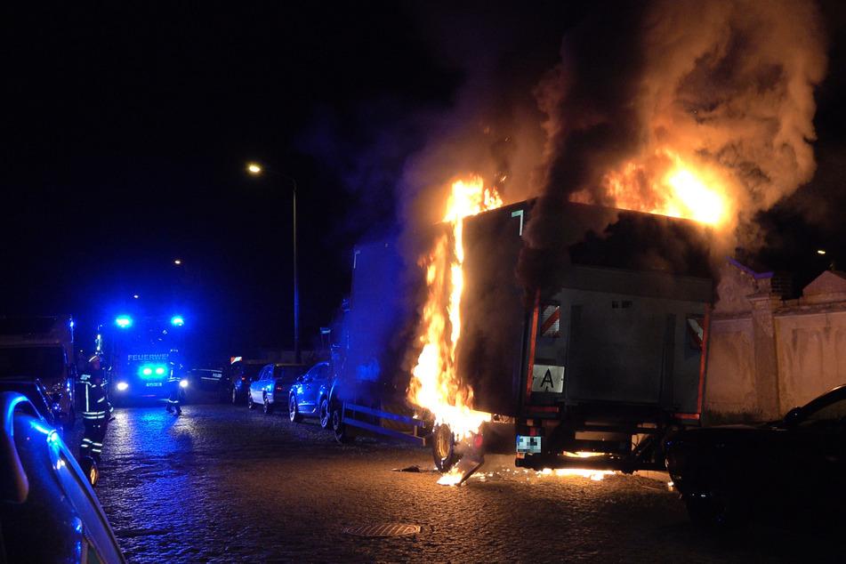 Auf der Franz-Mehring-Straße steht ein Lastwagen in Flammen. Auch er wurde Opfer eines Anschlags.