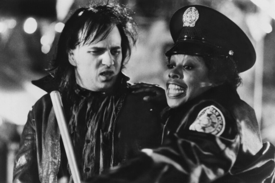 Marion Ramsey (†73, r.) with Bobcat Goldthwait (58) in Police Academy.