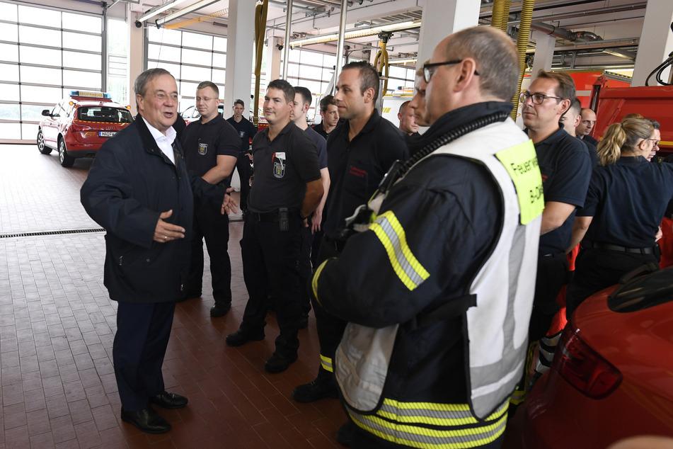 NRW-Ministerpräsident Armin Laschet (60, CDU, l) bedankt sich bei Hagenern Feuerwehrleuten für ihren Einsatz, nachdem er sich ein Bild von der Lage in der Stadt gemacht hat.