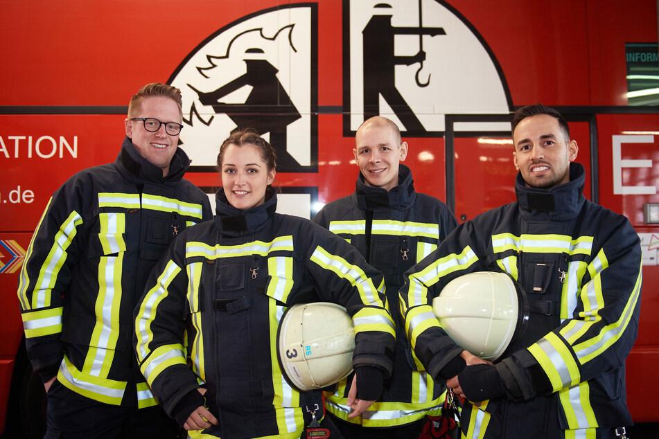 Feuerwehrfrau Jasmin steht zwischen ihren Kollegen Nick, Tim und Hilal (v.l) vor einem Feuerwehrfahrzeug.