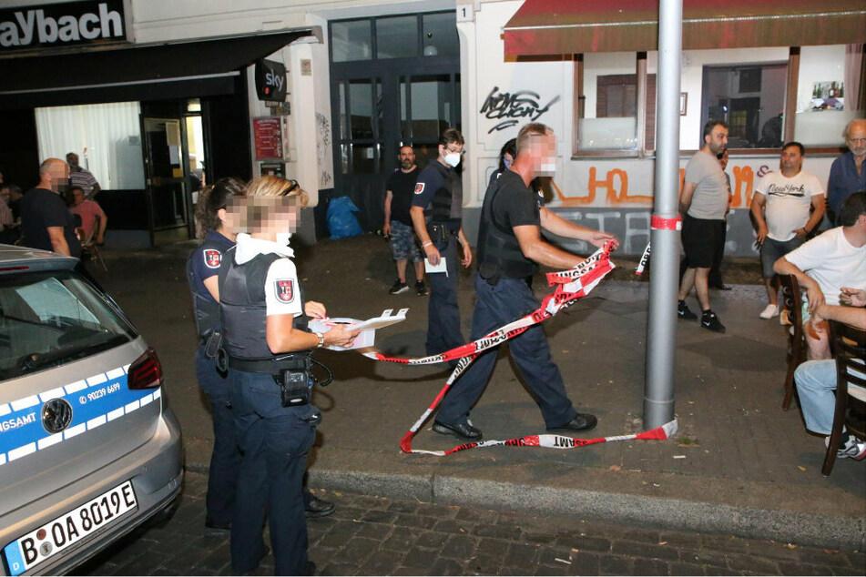Polizisten sperren den Bereich vor dem Lokal in Berlin-Neukölln mit Flatterband ab.