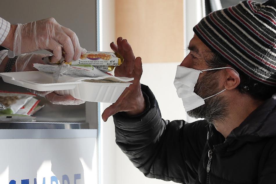 Mailand: Ein Freiwilliger reicht einem Obdachlosen mit Mund-Nasen-Schutz Essen. Landesweit sind verschärfte Corona-Schutzvorschriften in Kraft getreten. Doch es kann bald noch härter kommen.