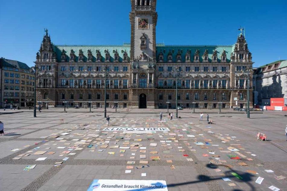 Zahlreiche Schilder und Plakate liegen während einer Aktion von Fridays for Future auf dem Rathausmarkt.