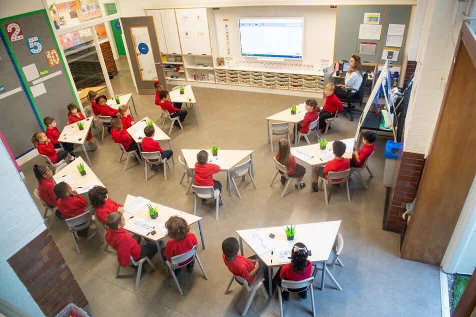 Schülerinnen und Schüler sitzen zusammen mit ihrer Lehrerin in einem Klassenzimmer.