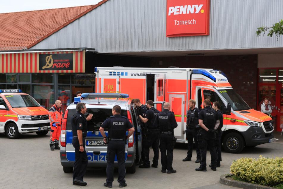 Einsatzkräfte stehen vor dem Penny-Markt in Tornesch.
