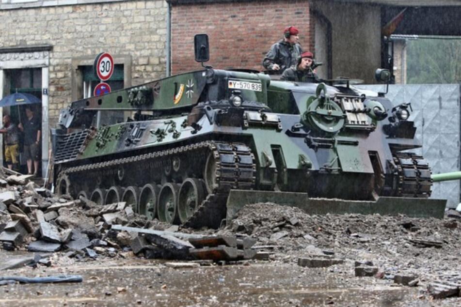 Ein Einsatzfahrzeug der Bundeswehr räumt in Aachen Geröll von der Straße.