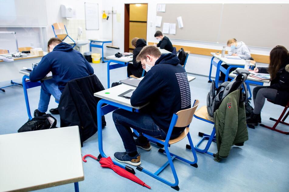 Schüler sitzen mit Mund-Nasen-Schutz in einem Klassenraum.
