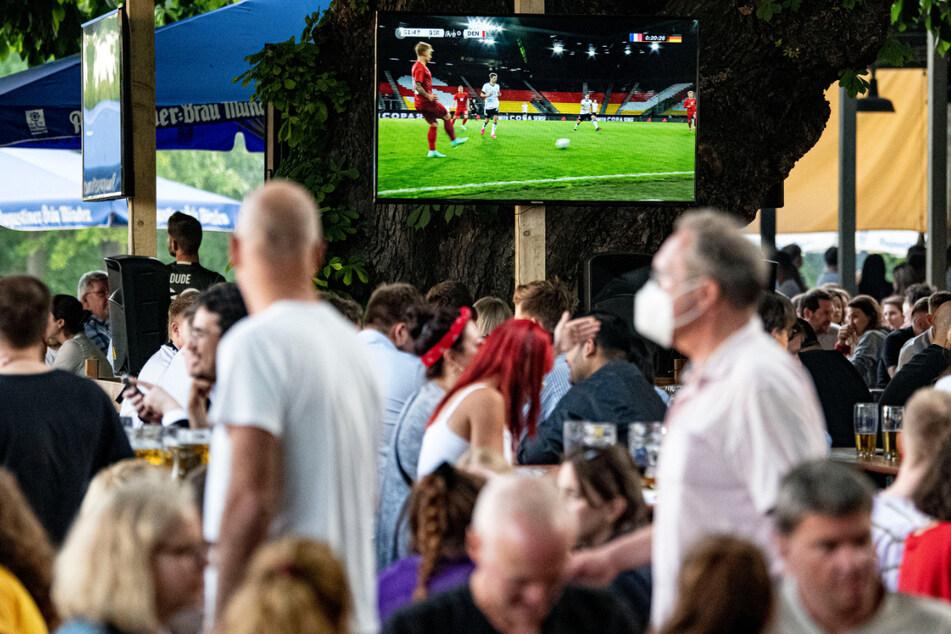 Fans verfolgen bei einem Public Viewing im Zollpackhof die Vorberichterstattung des Spiels auf einem Fernseher.