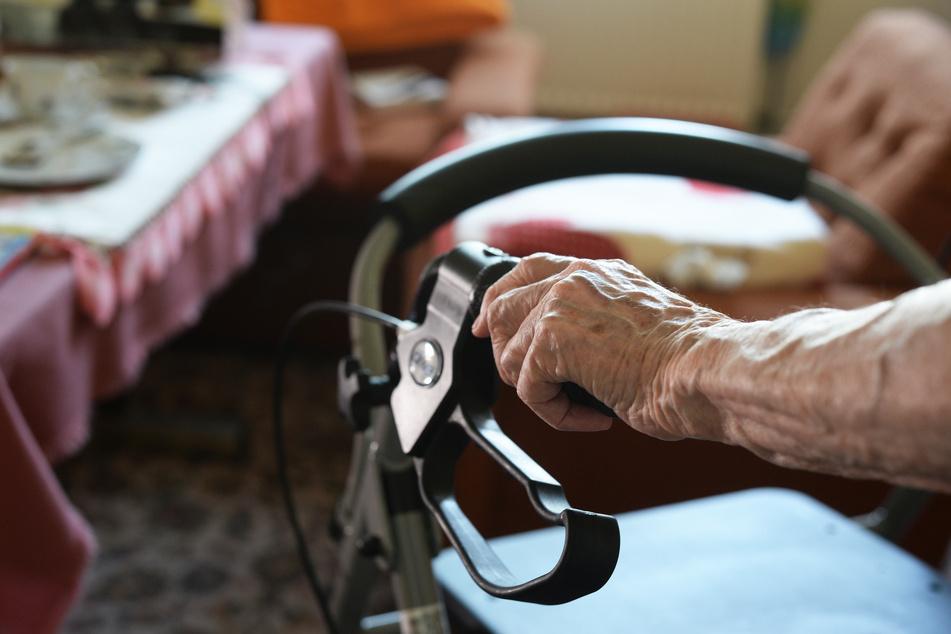 Eine ältere Frau geht an einem Rollator durch ihre Wohnung. (Symbolbild)
