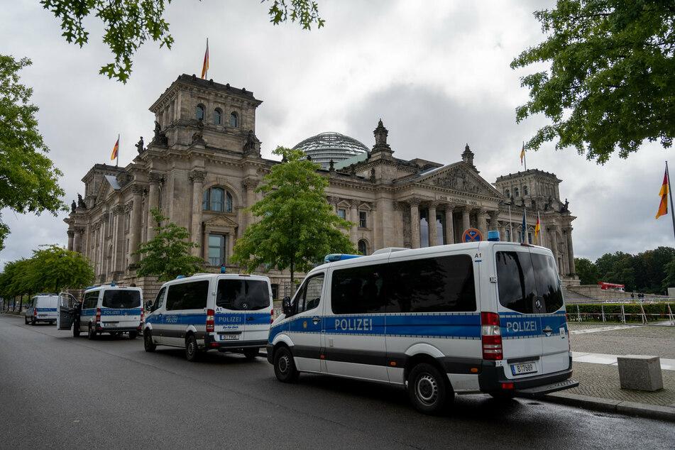Vor dem Reichstagsgebäude stehen Polizeiautos. Die Polizei hat das Regierungsviertel wegen angekündigten Querdenker-Demonstrationen gegen die Corona-Politik weiträumig abgesperrt.