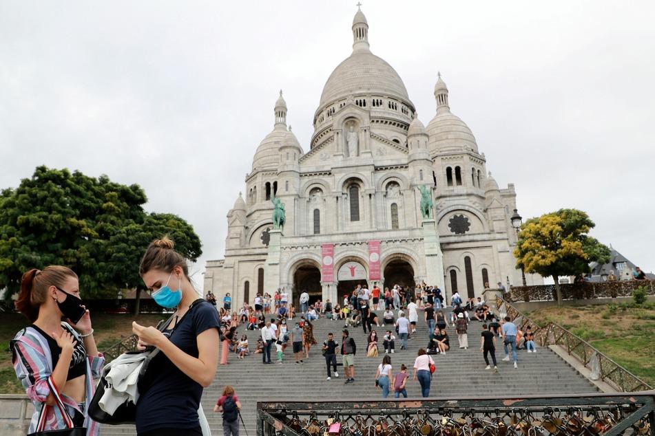Paris: Passanten stehen mit Mundschutz vor der Basilika Sacre Coeur.