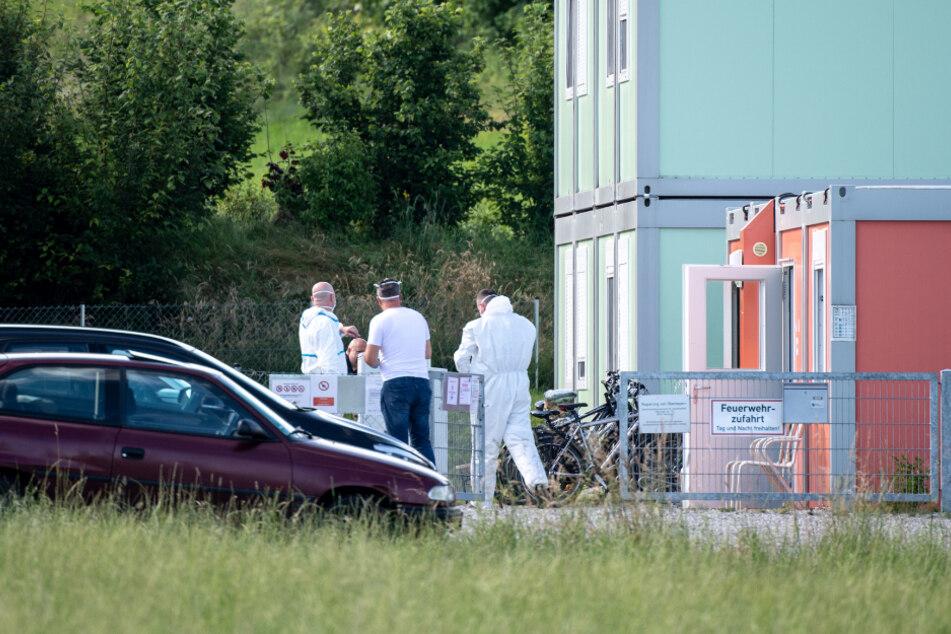 Mitarbeiter vom Landkreis Starnberg stehen in Schutzanzügen am Eingang einer betroffenen Wohncontaineranlage für Flüchtlinge in Pöcking.