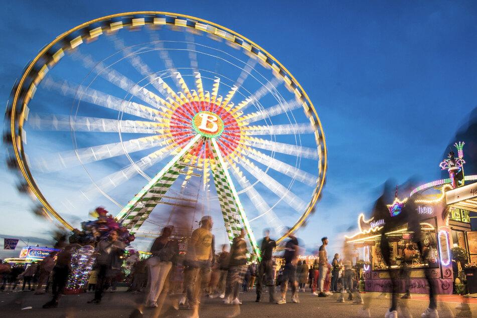 Besucher genießen 2019 zur blauen Stunde das 81. Stuttgarter Frühlingsfest auf dem Cannstatter Wasen. Diesen Frühling wird es wieder ausfallen.