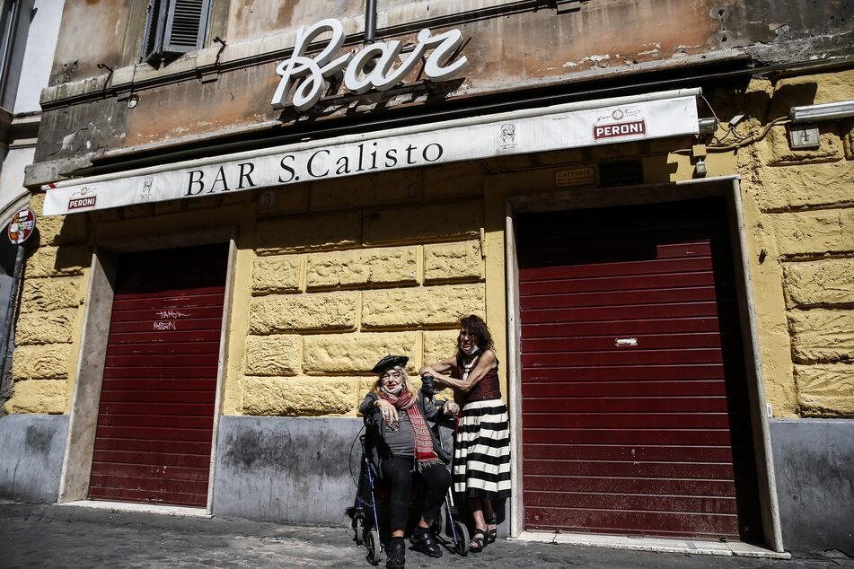 Frauen stehen vor einer geschlossenen Bar im Viertel Trastevere.