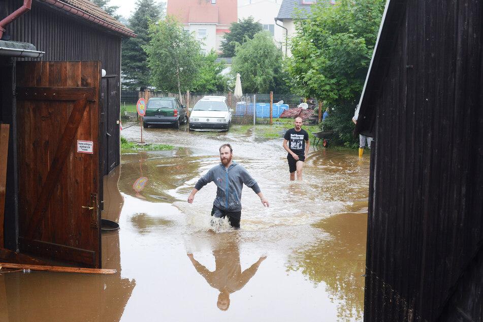 Ein Anwohner watet in Neukirch durch die Wesenitz, die sein Grundstück überflutet hatte.