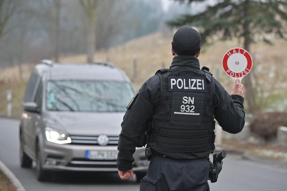 Vor dem Ortseingang an der Bahnhofstraße unterhalb von Seiffen zieht ein Polizist ein ortsfremdes Fahrzeug aus dem Verkehr.