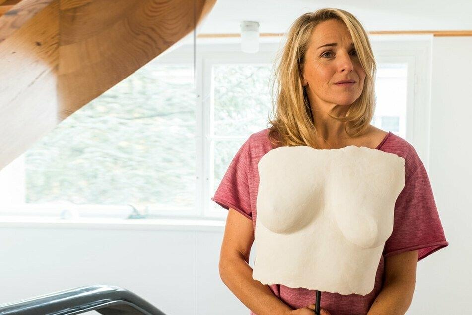 """Fritzie (Tanja Wedhorn) präsentiert Sohn und Ehemann den Gipsabdruck ihrer Brüste - eine Szene aus """"Der Himmel muss warten"""". Ihre Krebs-Diagnose war ein großer Schock."""