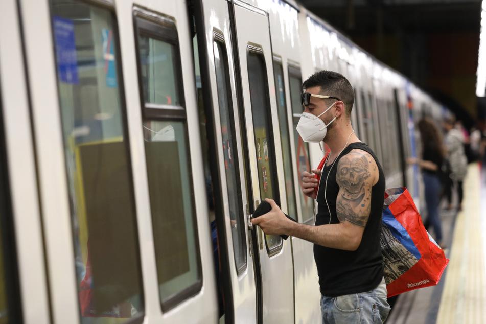 in Mann steigt in Madrid in eine U-Bahn ein. Barcelona und Madrid werden am Montag in die nächste Phase der Corona-Lockerungen eintreten.