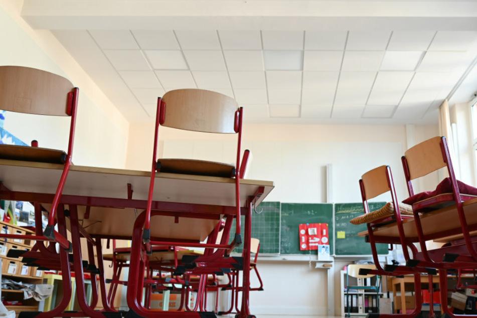 Stühle sind in einem leeren Klassenzimmer auf den Tischen abgestellt.