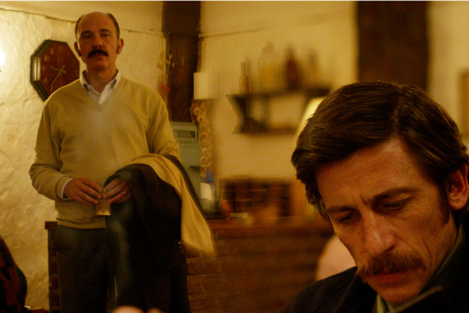 """Claudio Mora (Dario Grandinetti, l.) starrt den miesepetrigen Dieguito alias """"der Hippie"""" (Diego Cremonesi) im Restaurant an, nachdem er seinen Platz an ihn abgetreten hat. Wenig später kommt es zum Eklat."""