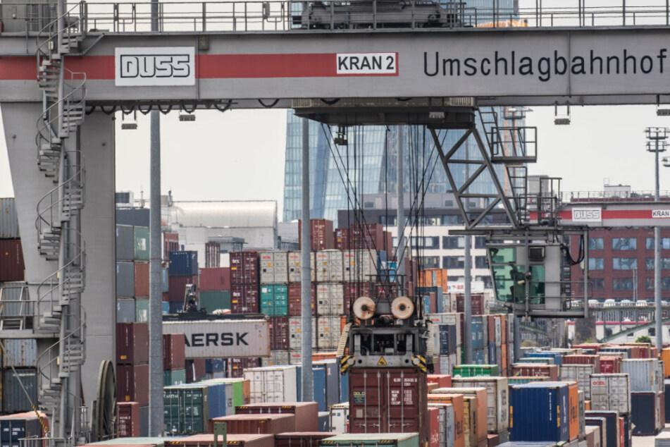 Container werden im Schatten der Zentrale der Europäischen Zentralbank (EZB, im Hintergrund) am Containerbahnhof Frankfurt-Ost verladen.