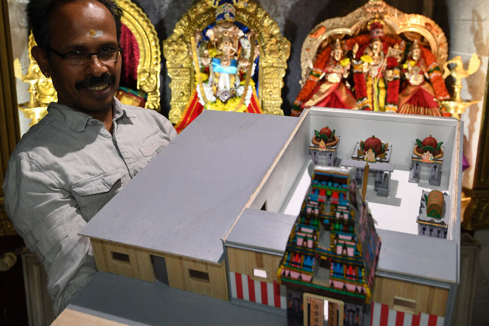 Pathmakaran Pathmanathan hält das Modell für den neuen Tempel in den Händen.