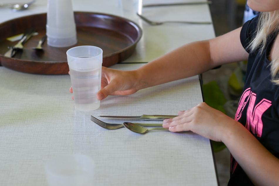 Ein Mädchen wartet in der Ferienanlage in der Perspektivfabrik am Beetzsee an ihrem Platz am Esstisch mit einem Becher Wasser und ihrem Besteck, bis sie sich das Essen an der Ausgabe holen kann.