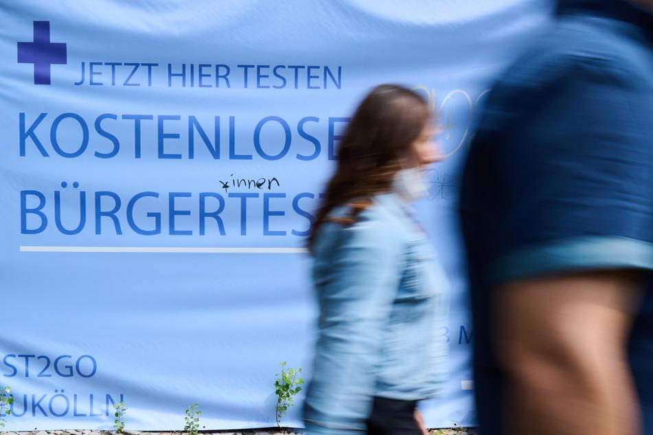 """""""Kostenlose Bürgertests"""" steht auf einem Plakat während Personen vorüber gehen."""