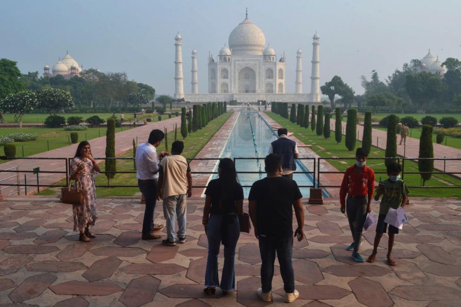 Agra: Touristen stehen am Wasserbecken vor dem Mausoleum Taj Mahal, das im Hintergrund zu erkennen ist.