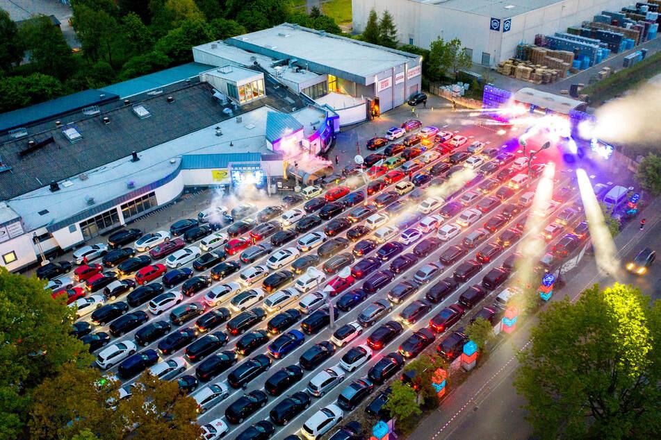 Gäste parken mit ihren Autos während einer Auto-Disco auf dem Parkplatz einer Diskothek. So ähnlich könnte auch die Zeugnisausgabe des Louise-Henriette-Gymnasium in Oranienburg aussehen.