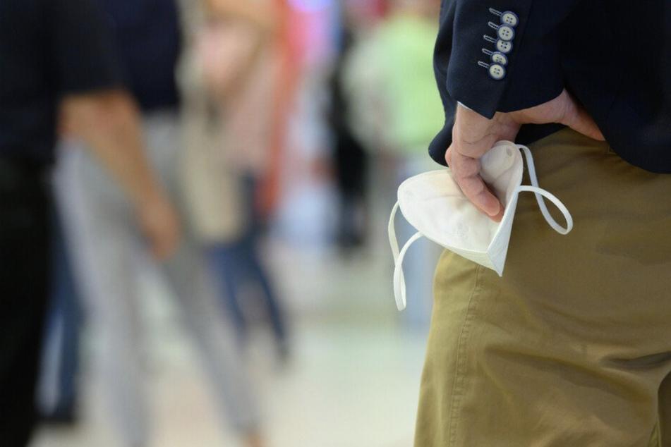 Ein Mann hält seine FFP2-Maske in der Hand. Künftig muss diese beim Einkaufen in Leipzig wieder dabei sein.