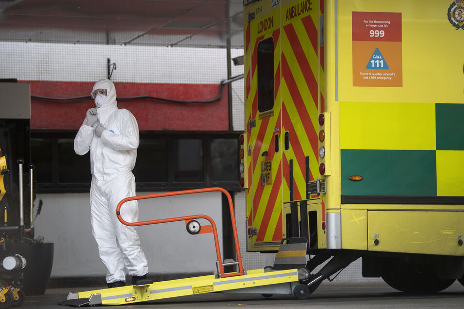 Ein Sanitäter im Schutzanzug steht vor einem Rettungswagen, der einen Patienten in das St Thomas Krankenhaus bringt.