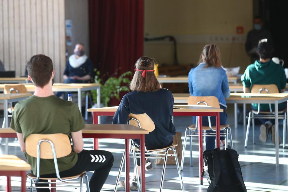 Schüler mit Mundschutz sitzen bei der Prüfungsvorbereitung fürs Abitur in einer zum Schulraum umfunktionierten Turnhalle in der JenaPlan Schule.