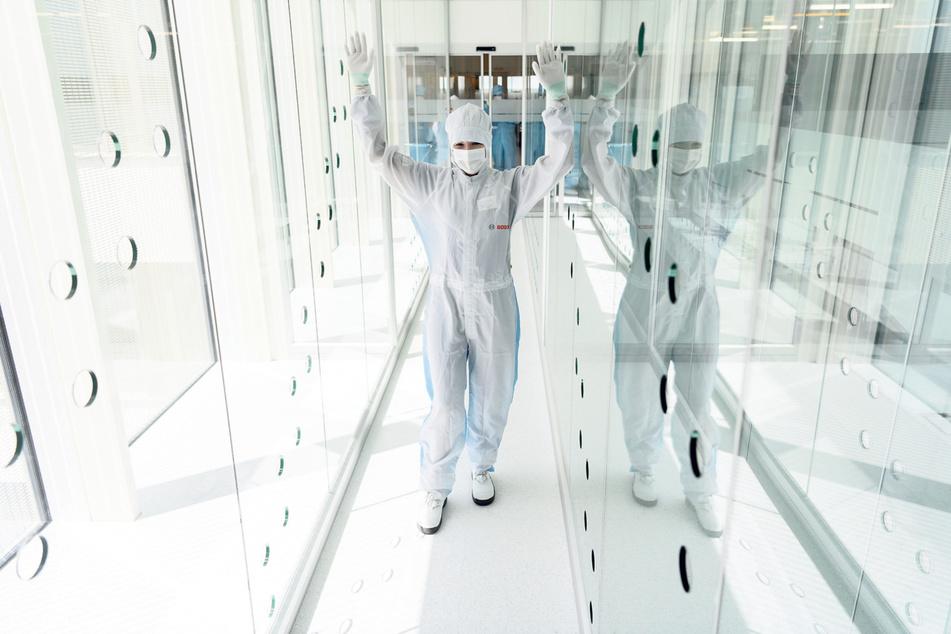 Eine Mitarbeiterin im Schutzanzug wird vorm Zutritt in den Reinraum in diesem Gang noch sauber geblasen.