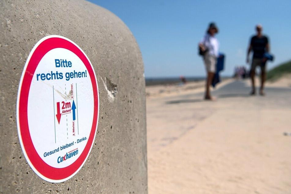 Hier weist ein Schild am Strand in Cuxhaven auf die Sicherheitsabstände sowie die vorgeschriebenen Laufrichtungen hin.