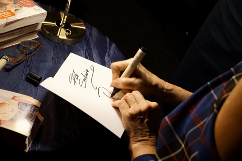 Frau Nick nach einem Auftritt beim Autogramme-Schreiben.