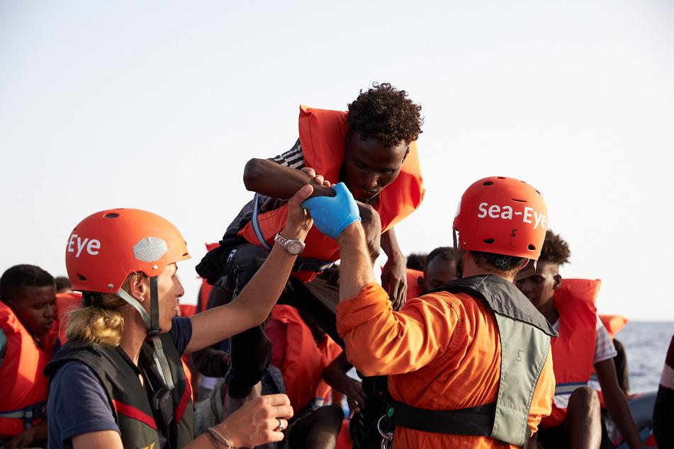 Die von der Seenotrettungsorganisation Sea-Eye herausgegebene Aufnahme zeigt Seenotretter, die Flüchtlinge im Mittelmeer von einem Schlauchboot evakuieren.