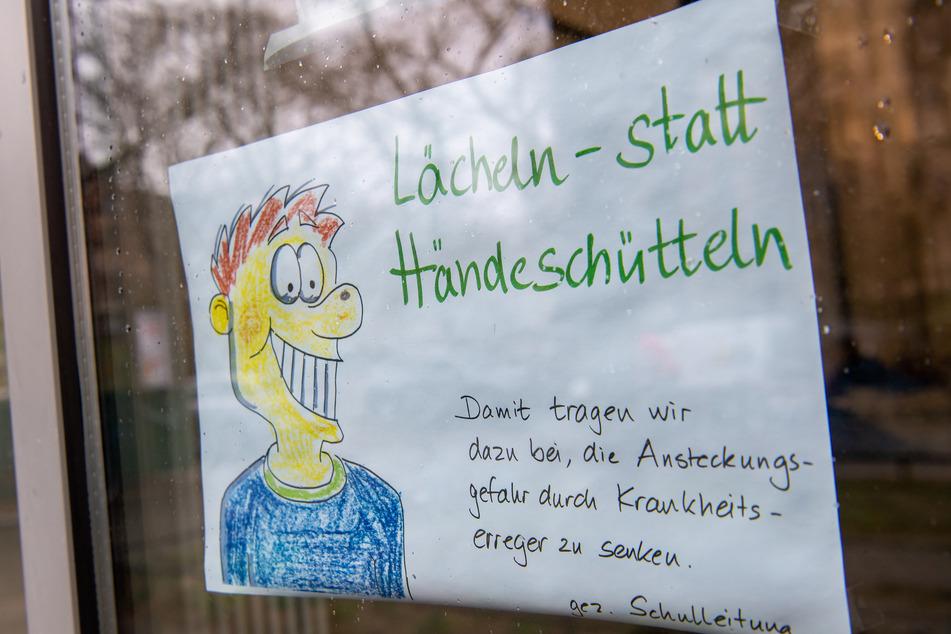 """Ein gemaltes Schild mit der Aufschrift """"Lächeln statt Händeschütteln- Damit tragen wir dazu bei, die Ansteckungsgefahrt durch Krankheitserreger zu senken - gez. Schulleitung"""" hängt an der Tür eines Grundschule."""
