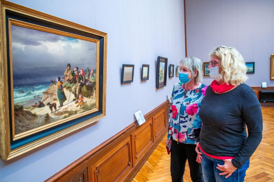 Zwei Besucherinnen mit Mundschutz stehen vor einem Gemälde in der Gemäldesammlung im Staatlichen Museum Schwerin.