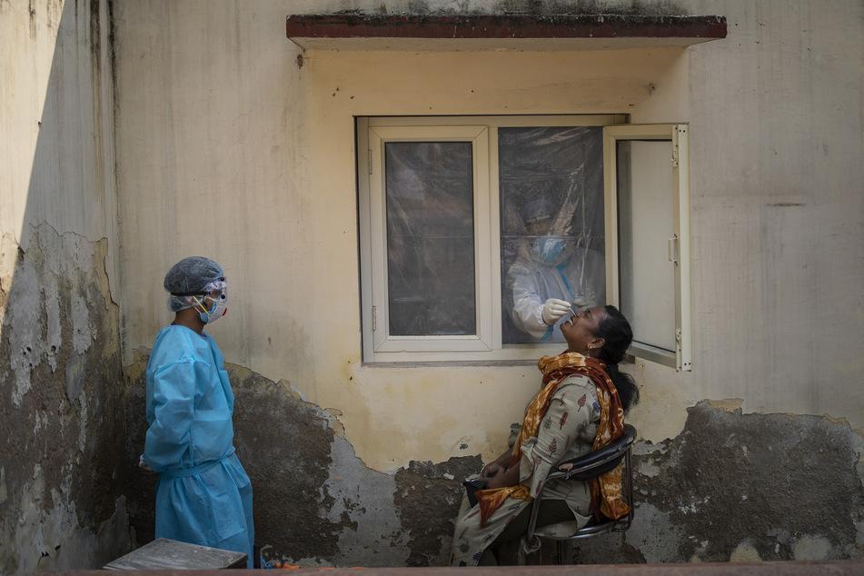 Ein mit einem Schutzanzug bekleideter Mitarbeiter des Gesundheitswesens nimmt bei einer Frau in einem Covid-19-Testzentrum eine Nasenabstrichprobe.