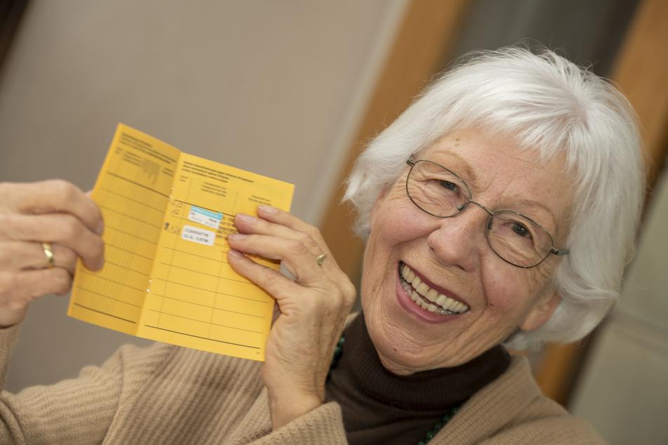 Seniorin Ursula Neuberger hält ihren Impfpass, in dem eine Grippe-Impfung (oben) und ihre erste Corona-Impfung vermerkt sind.