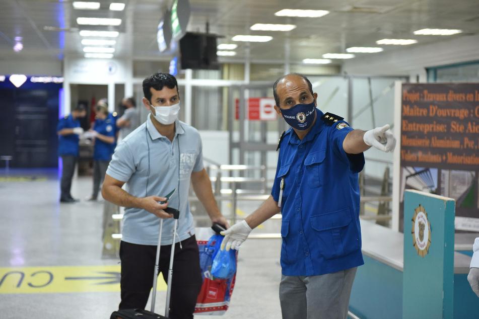 Ein Flughafenmitarbeiter zeigt einem Passagier am Flughafen Tunis-Carthage den Weg.