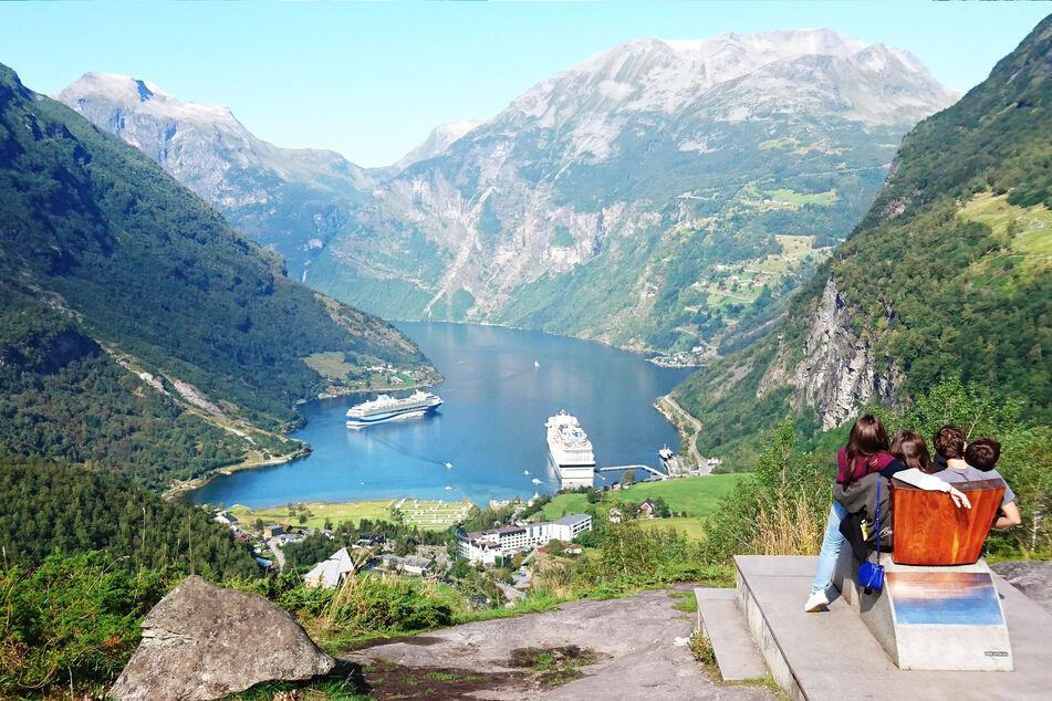 Personenen schauen runter in den Geirangerfjord im Südwesten Norwegens auf die dort liegenden Kreuzfahrtschiffe.