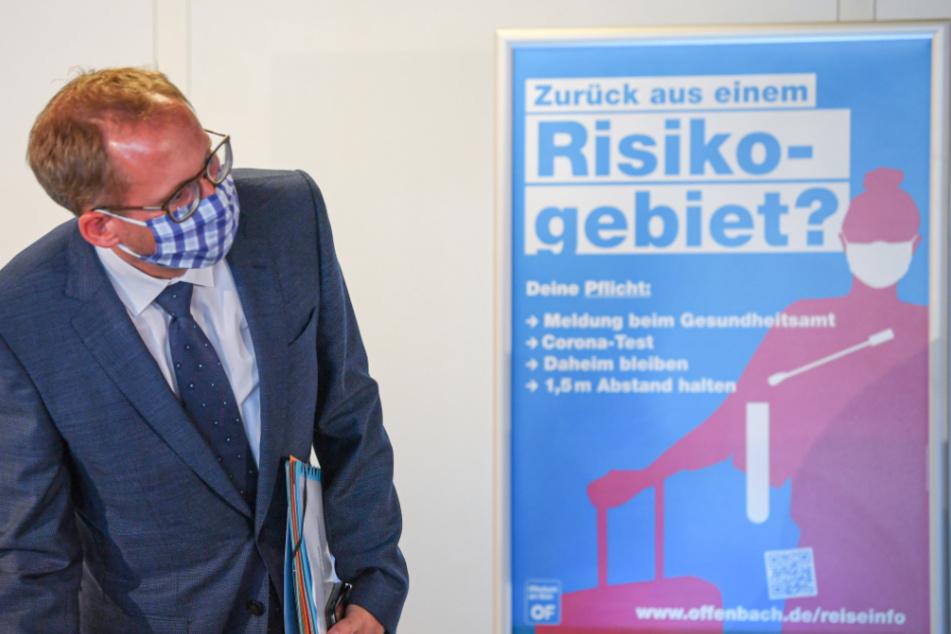 """Kai Klose (Bündnis 90/Die Grünen), Sozialminister des Landes Hessen, steht am Freitag zu Beginn einer Pressekonferenz im Offenbacher Stadion neben einem Plakat mit der Aufschrift """"Zurück aus einem Risikogebiet?""""."""