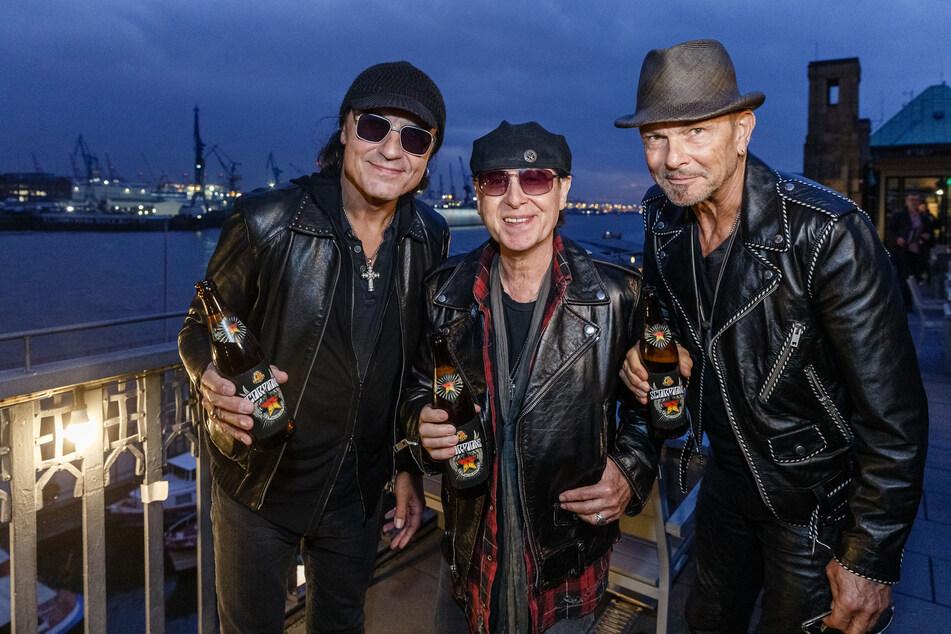 Die Musiker der Rockgruppe Scorpions Matthias Jabs (l-r), Klaus Meine und Rudolf Schenker präsentieren ein Bier, das ihren Namen trägt - ganz ohne Maske, dafür aber mit breitem Grinsen.