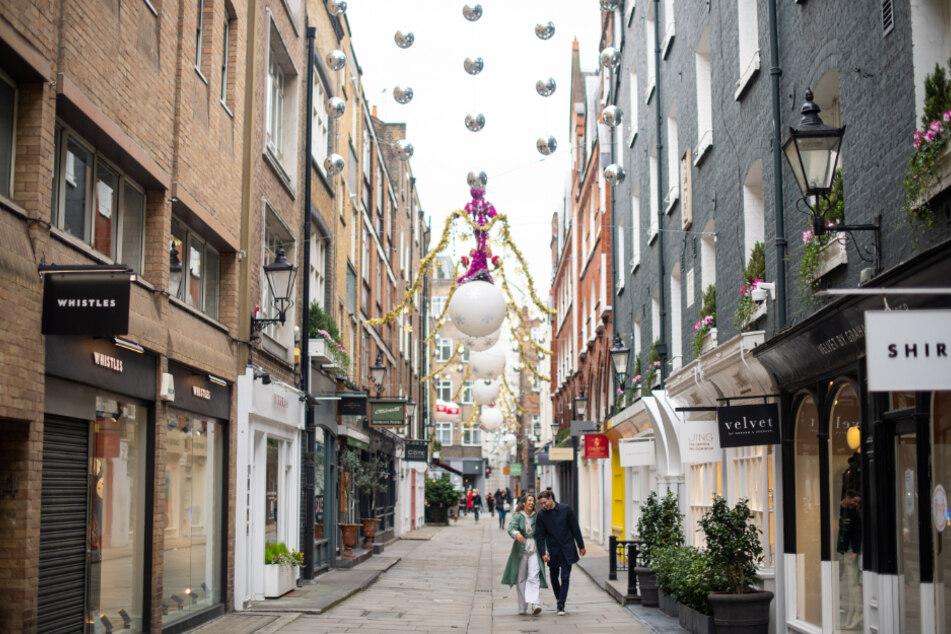 London: Passanten gehen durch die festlich dekorierte Fußgängerzone St Christopher's Place vorbei an geschlossenen Geschäften.