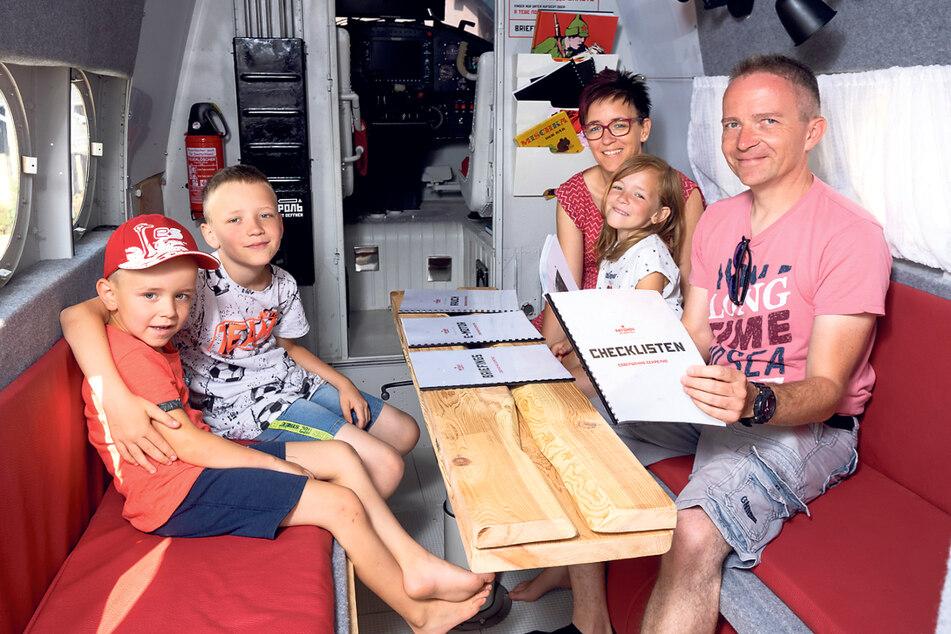 """Platz ist im kleinsten Flieger: Kurt (6) und Oskar (11, auf der linken Bank) und Mama Silvana (45), Luise (8) und Papa Andre Horn (49) in der """"Sitzecke""""."""