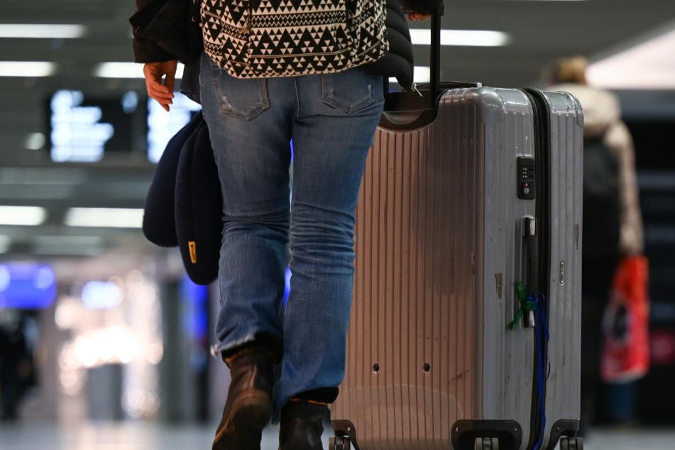 Hessen, Frankfurt/Main: Eine Flugreisende schiebt ihren Koffer an den geschlossenen Geschäften im Terminal 1 des Frankfurter Flughafens vorbei.